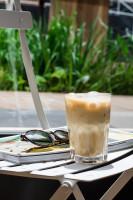 Stuhl, auf dem eine Zeitschrift, eine Sonnenbrille und ein Kaffee steht