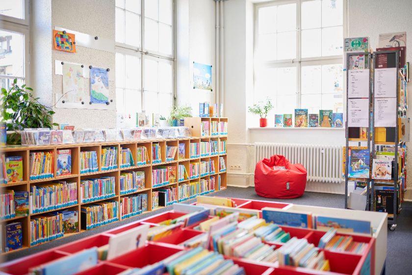 Büchertröge und niedrige Bücherregale mit Kinderbüchern darin, roter Sitzsack und Pflanzen, große helle Fenster