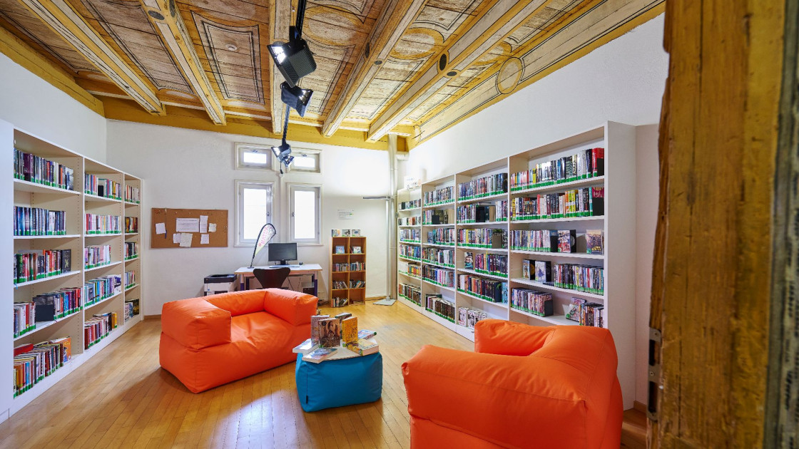 Bücherregale an den Wänden. In der Mitte ist eine Sitzgruppe