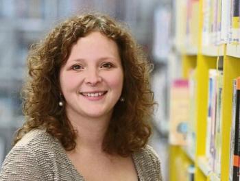 Bild der Büchereileitung Ulrike Höllwarth neben einem Bücherregal